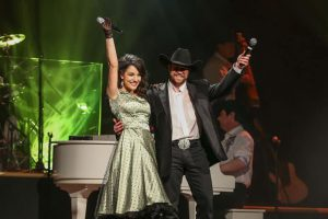 Woman in green dress and man in black jacket and black cowboy hat on stage